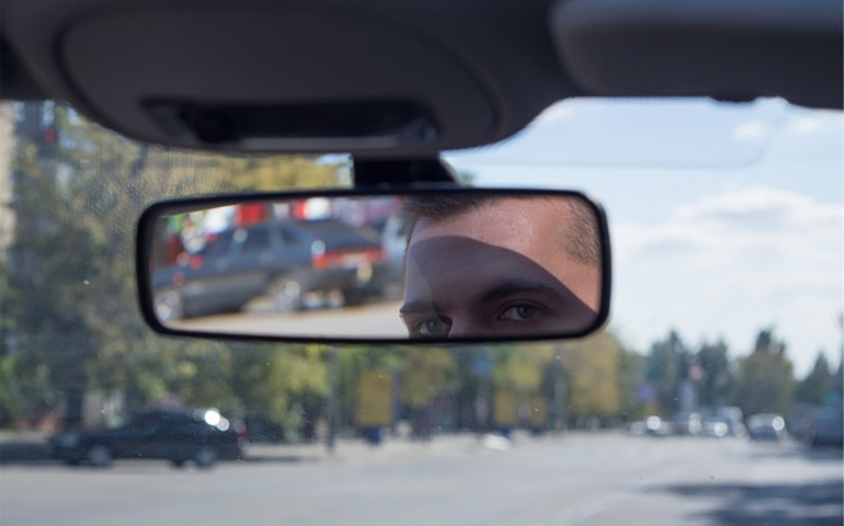 Man Looking in Rearview Mirror